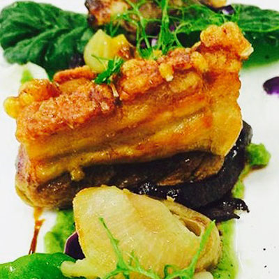 Beautiful sun-tanned beer-braised pork belly with caramelised apples